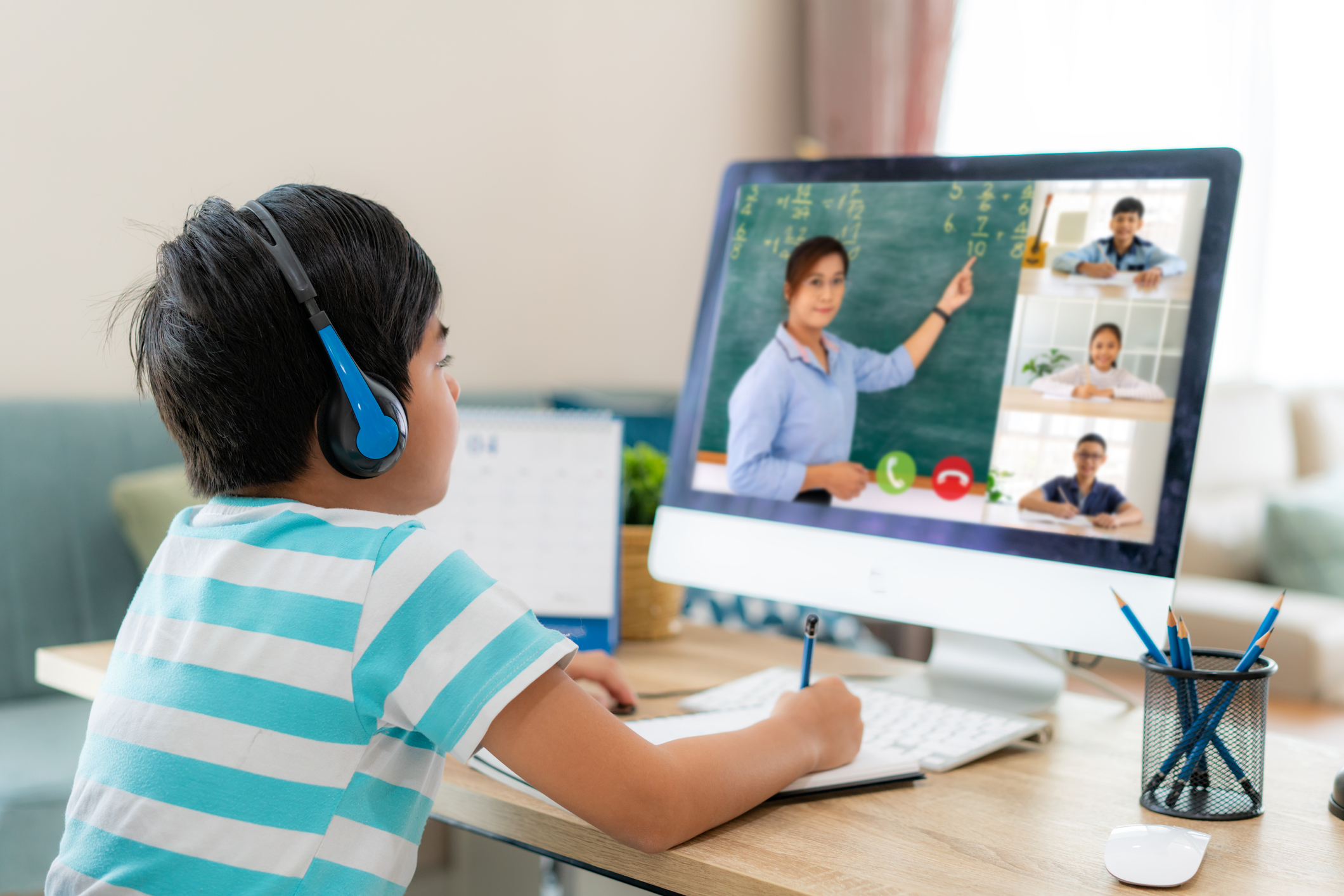 Asian boy student video conference e-learning with teacher and classmates on computer in living room at home.