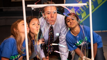 Curious Crew - Image of host with students doing an experiment.